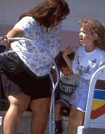 Woman wearing black shorts listening to child at amusement park.