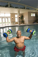 Man exercising with dumbbells in pool and improving his energy levels.